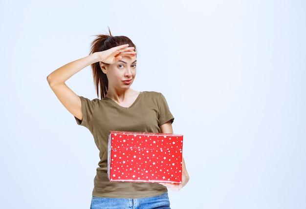 Giovane donna che tiene in mano una confezione regalo rossa e si diverte molto