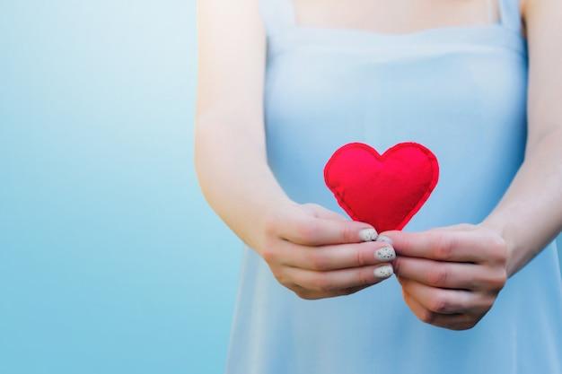 Giovane donna che tiene un cuore rosso in sue mani sul blu