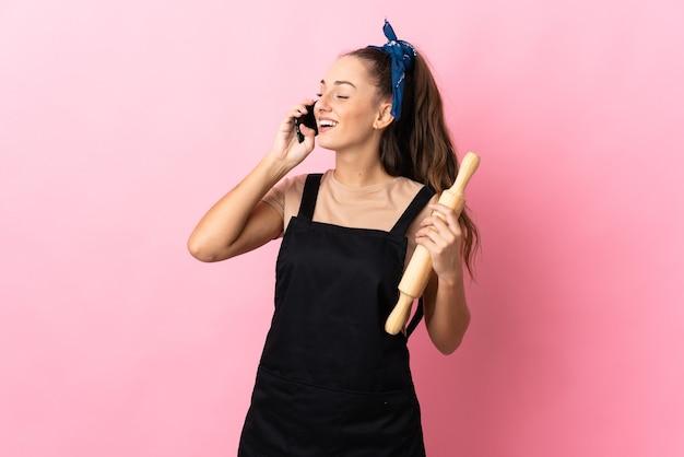 Giovane donna in possesso di un mattarello che tiene una conversazione con il telefono cellulare