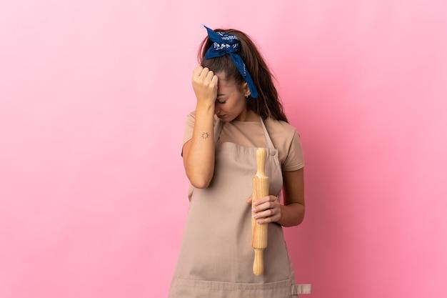 Giovane donna che tiene un mattarello con mal di testa