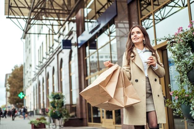 Sacchetti di shopping della holding della giovane donna nella via della città. la signora sorridente sta correndo con le grandi borse in metropoli consumismo, acquisto, vendite, concetto di stile di vita