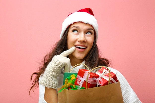 Giovane donna che tiene la borsa della spesa con i regali di natale su sfondo rosa