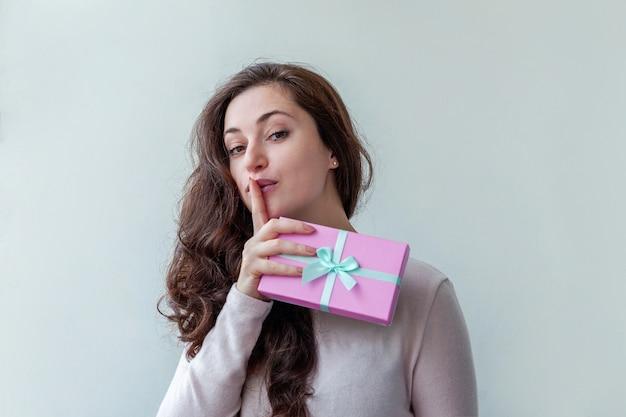 Giovane donna che tiene piccola confezione regalo rosa isolato su sfondo bianco