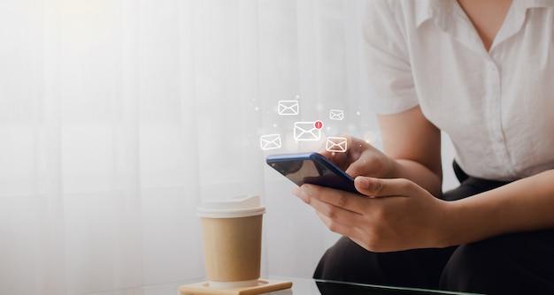 Giovane donna che tiene in mano uno smartphone che invia messaggi elettronici e controlla la posta elettronica online sul web con il concetto di tecnologia con l'icona della scatola.