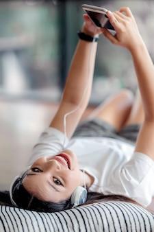 Smartphone della tenuta della giovane donna, esaminando macchina fotografica e sorridendo mentre trovandosi sul letto a casa