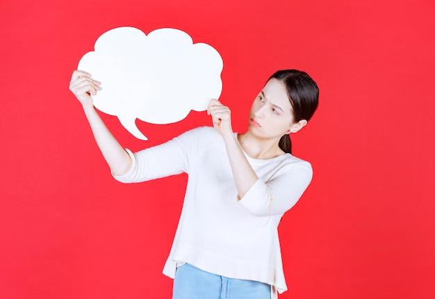 Giovane donna che tiene il fumetto a forma di nuvola cloud