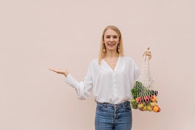 Giovane donna che tiene la borsa della spesa della stringa con la frutta su un fondo beige.