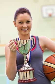 Giovane donna che tiene un trofeo e una palla da basket