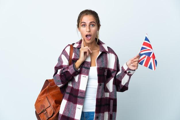 Giovane donna che tiene una bandiera del regno unito isolata che intende realizzare la soluzione