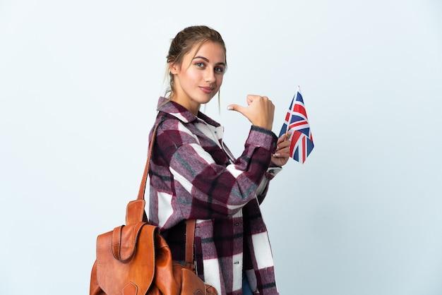 Giovane donna che tiene una bandiera del regno unito isolata sul muro bianco orgoglioso e soddisfatto di sé