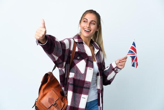 Giovane donna che tiene una bandiera del regno unito su bianco dando un pollice in alto gesto