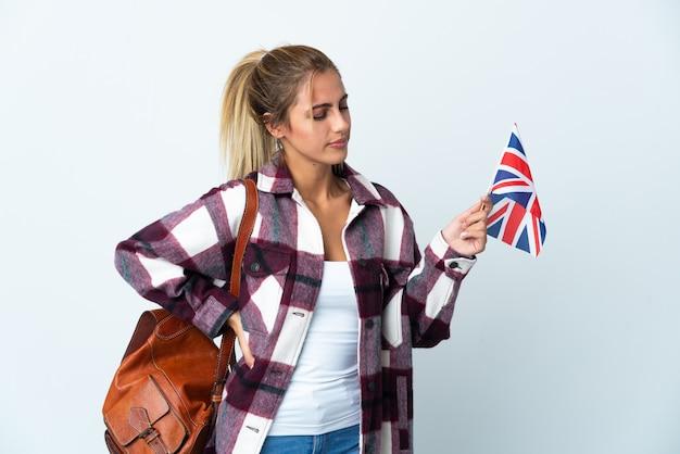 Giovane donna che tiene una bandiera del regno unito su bianco che soffre di mal di schiena per aver fatto uno sforzo