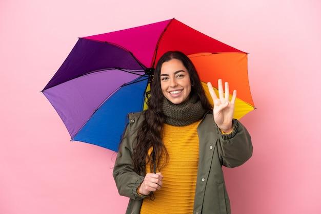 Giovane donna che tiene un ombrello isolato su sfondo rosa felice e contando quattro con le dita