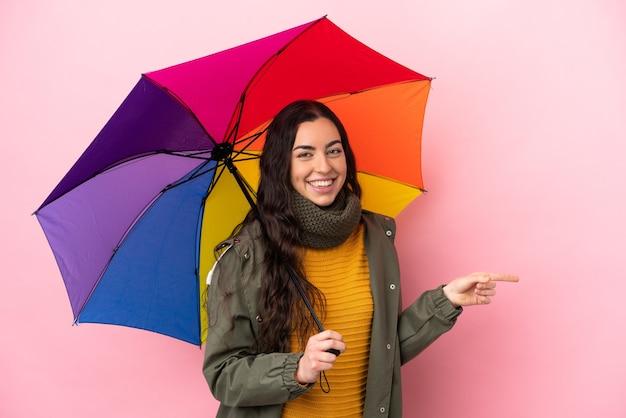 Giovane donna che tiene un ombrello isolato su sfondo rosa che punta il dito a lato