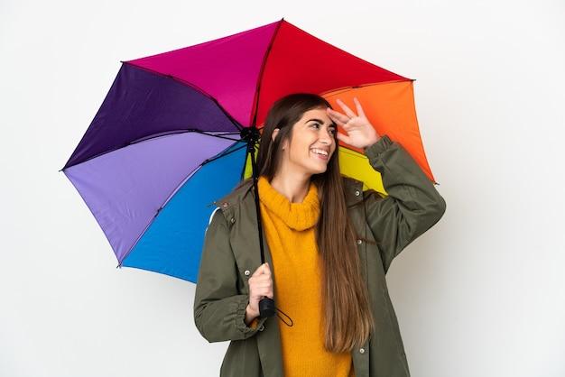 Giovane donna che tiene un ombrello isolato sulla parete bianca che sorride molto