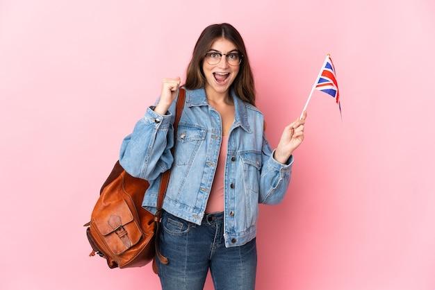 Giovane donna che tiene una bandiera del regno unito isolata sul colore rosa che celebra una vittoria nella posizione del vincitore