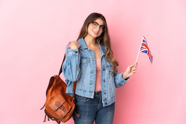 Giovane donna che tiene una bandiera del regno unito isolata sulla risata rosa