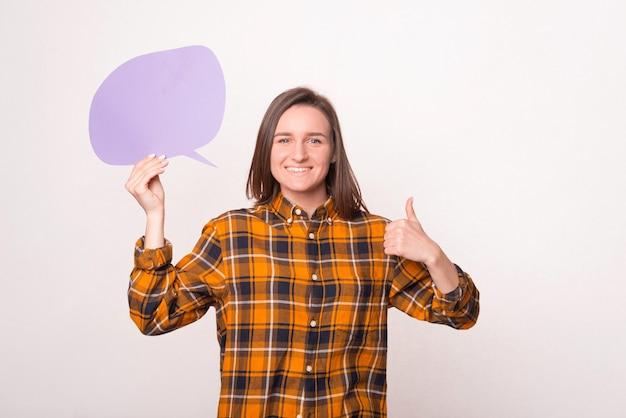 Giovane donna che tiene il fumetto vuoto viola e che mostra il pollice in su