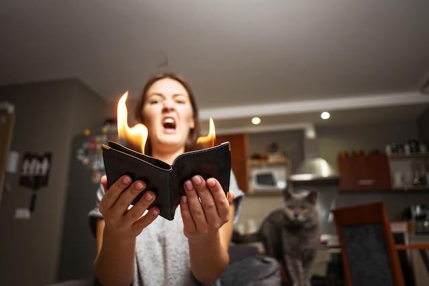 Giovane donna che tiene un portafoglio, portafoglio in fiamme, ragazza sorpresa, fuoco concetto magico, portafoglio sta bruciando fuoco