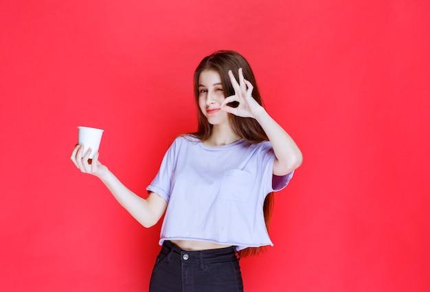 Giovane donna che tiene una tazza di acqua usa e getta bianca e che mostra il segno di soddisfazione.