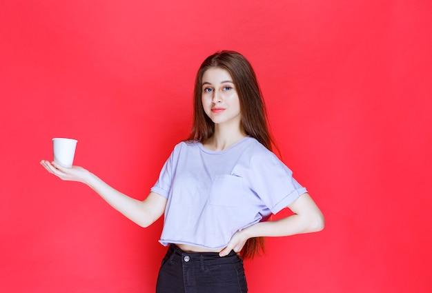 Giovane donna che tiene una tazza di acqua usa e getta bianca.