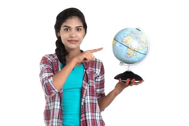 Giovane donna che tiene il globo del mondo e posa su un muro bianco.