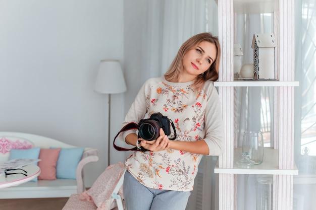 Una giovane donna tiene in mano una macchina fotografica e distoglie lo sguardo
