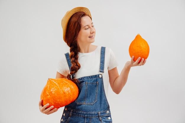 La giovane donna tiene un raccolto di zucche arancioni su uno sfondo bianco mentre ne guarda una