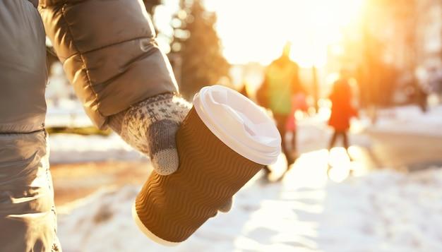 La giovane donna tiene la tazza di caffè da asporto nel parco invernale
