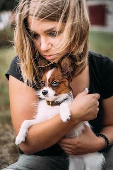 Una giovane donna tiene tra le braccia un piccolo cucciolo papillon bianco e testa marrone.