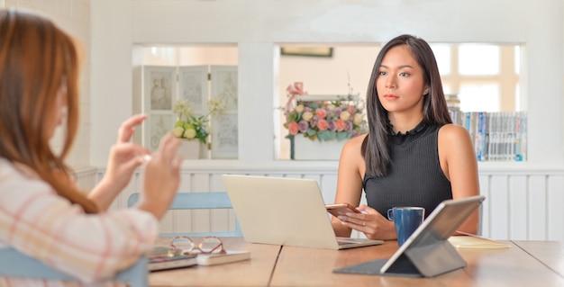 La giovane donna tiene uno smartphone in mano e un laptop con tablet sul tavolo