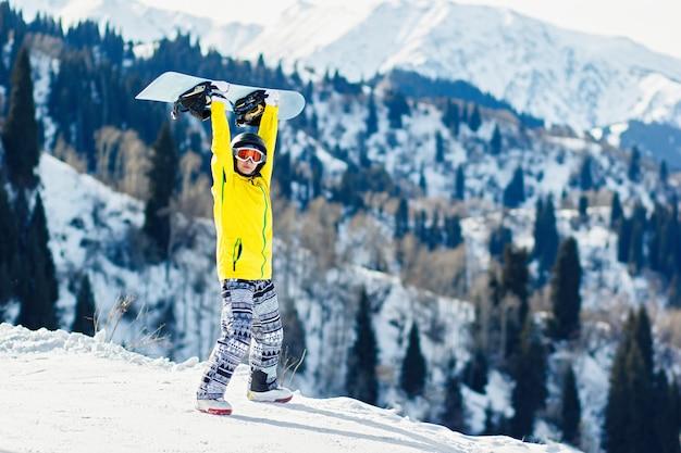 La giovane donna tiene uno snowboard sopra la sua testa su uno sfondo di montagne