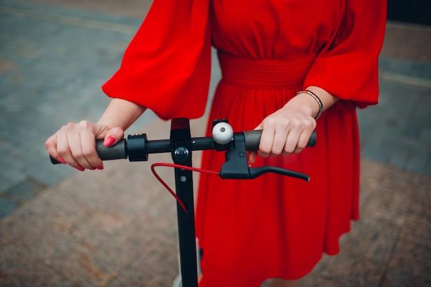 La giovane donna tiene il volante del motorino elettrico in vestito rosso alla città.