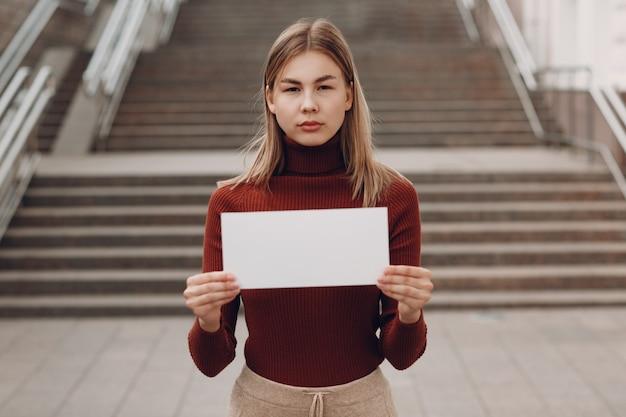 La giovane donna tiene in mano il libro bianco sullo sfondo della strada delle scale. due donne che parlano a tavola in street cafe. foglio modello vuoto bianco con spazio vuoto.