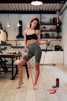 Esercizio domestico della giovane donna con un espansore.