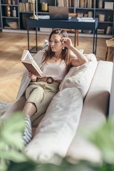 Giovane donna a casa sdraiata sul divano e leggendo il libro.