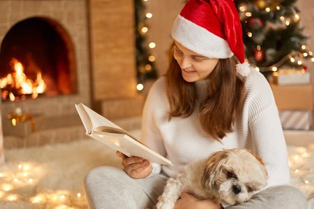 Giovane donna a casa leggendo un libro con il cane in ginocchio, guardando le pagine, indossando abiti casual e cappello rosso festivo, in posa in soggiorno con camino e albero di natale