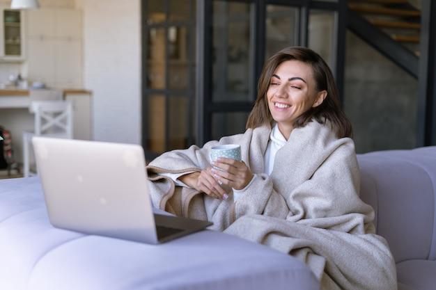 Giovane donna a casa su un divano in inverno sotto un'accogliente coperta con un laptop, guardando serie comiche