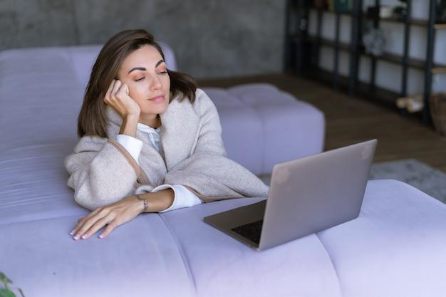 Giovane donna a casa sul divano in inverno sotto un'accogliente coperta con un laptop, guardando un film