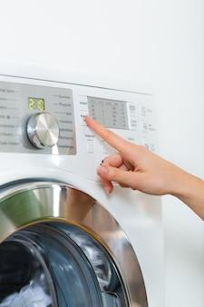 La giovane donna o la governante ha un giorno di lavanderia a casa, seleziona il programma