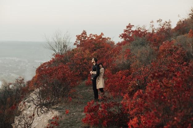 Giovane donna che abbraccia il suo ragazzo da dietro contro la foresta di autunno