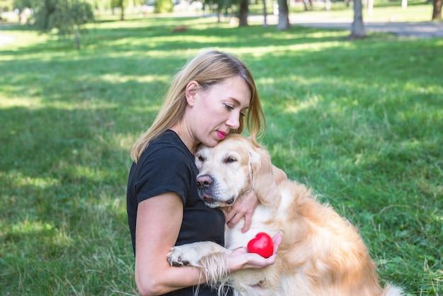 La giovane donna abbraccia il suo cane da riporto che tiene in mano un cuore rosso. concetto di protezione degli animali.