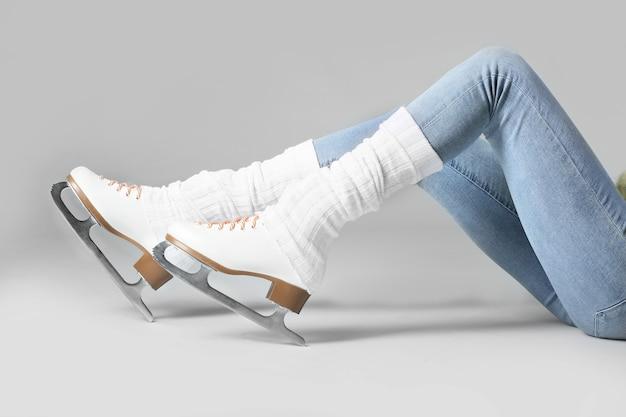 Giovane donna in scarpe da pattino da ghiaccio sulla superficie grigia