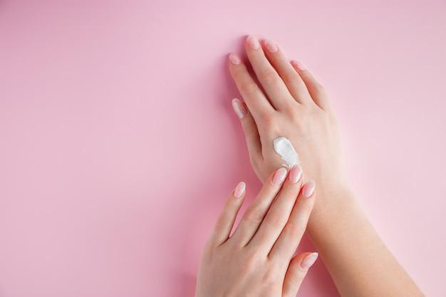 Una giovane donna si sta applicando la crema alle mani concetto di spa e cura del corpo su uno sfondo rosa