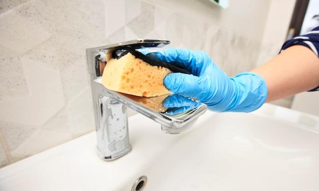 La giovane donna sta pulendo il rubinetto del bagno