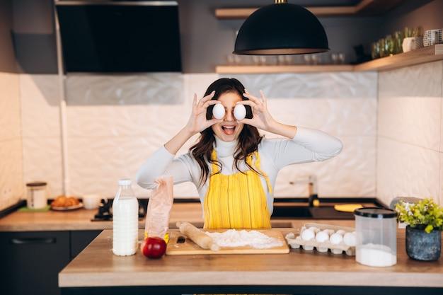 La giovane donna sta coprendosi gli occhi dalle uova mentre cucina in cucina. la casalinga sta avendo la pistola mentre cucina.