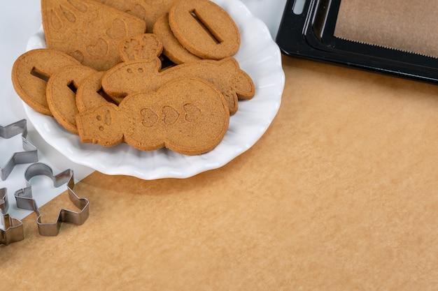 La giovane donna sta decorando il biscotto dei biscotti della casa di pan di zenzero di natale a casa con la copertura di glassa in un sacchetto di glassa, primo piano, stile di vita.