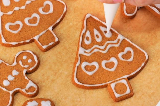La giovane donna sta decorando il biscotto dei biscotti della casa di pan di zenzero di natale a casa con la glassa nella borsa della glassa, fine su, stile di vita.