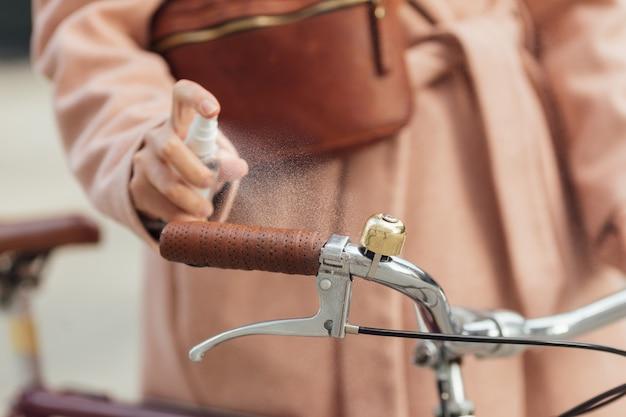 La giovane donna sta disinfettando con disinfettante spray sul manubrio della bicicletta