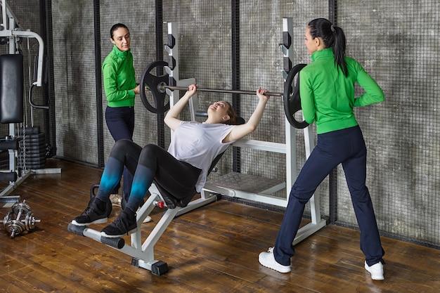 La giovane donna sta facendo la panca con il supporto di due assistenti